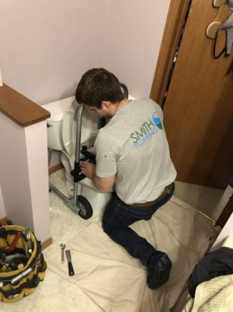 Craig Smith working on installing a new toilet in Pierre SD